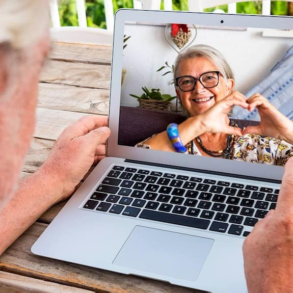 An older woman is interacting with a younger woman on her laptop. The younger woman is making the shape of a heart with her hands.