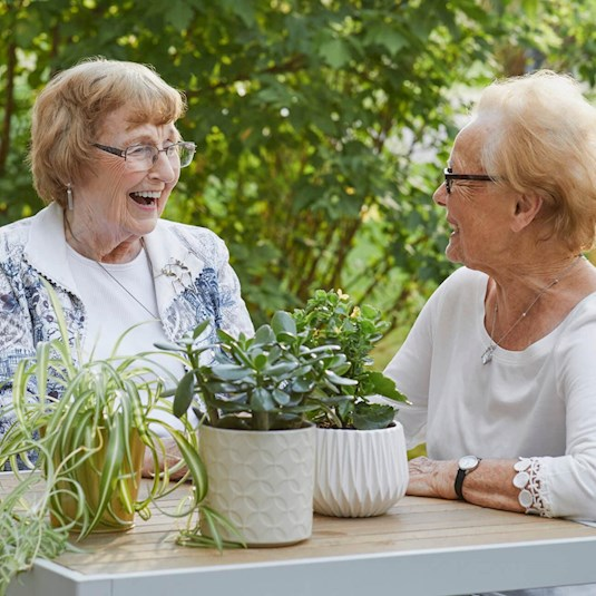 Two older women sitting at a table laughing