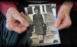 An older woman's hands holding a photo of herself as a young woman in her miltary uniform.