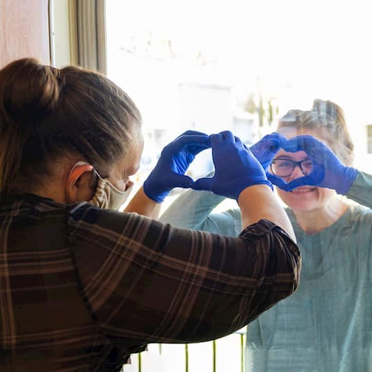 A health care worker and a visitor make heart shapes with their hands through the window