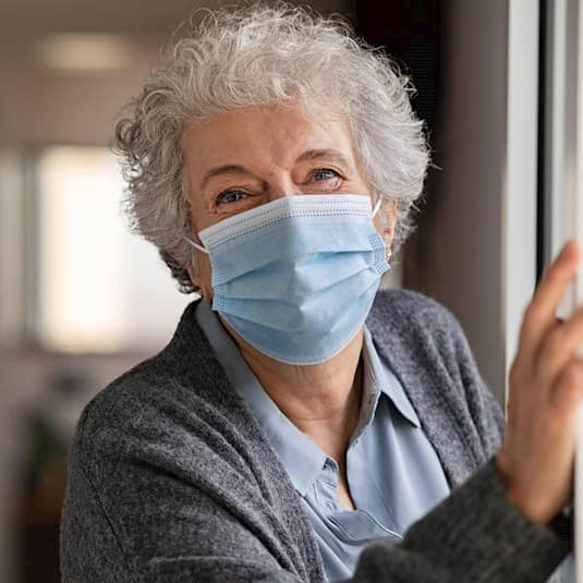An older woman standing in her dooray, you can see her smile in spite of the mask she's wearing.