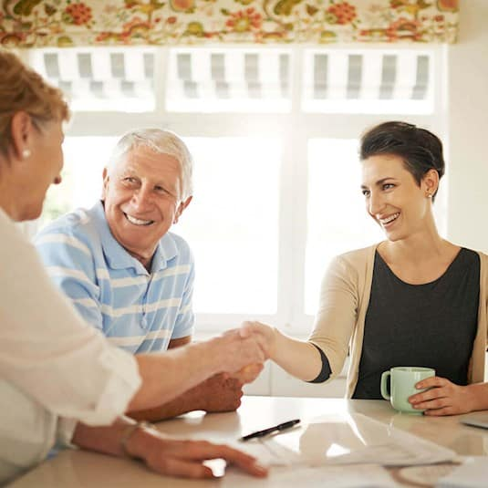 an older woman shakes hands with a younger woman, while an older man looks on