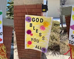 Signs reading Thank you! 4 Working, God Bless You All, and Be Safe Be Strong Together outside McKenzie Towne Continuing Care in Alberta