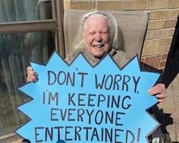 Resident holding sign that says don't worry I'm keeping everyone entertained