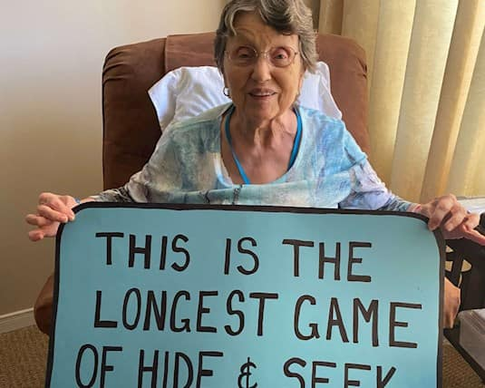 resident holding sign that reads this is the longest game of hide and seek ever!