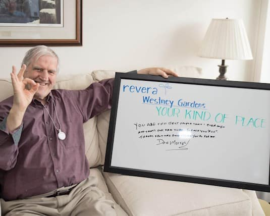 """A resident holds a sign which reads """"You are the best people that I ever met... thanks for the good things you do for me."""""""