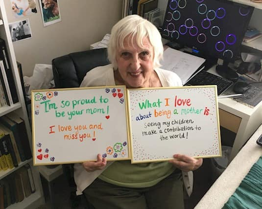 """A resident holds a sign reading """"What I love about being a mother is seeing my children make a contribution to the world."""""""