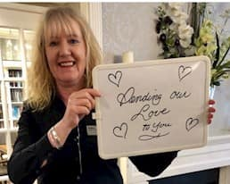 """Staff member holding sign """"sending our love to you"""""""