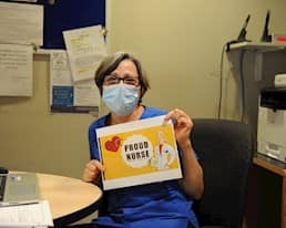 Employee holding sign that reads proud nurse