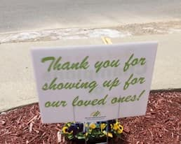 """A sign reading """"Thank you for showing up for our loved ones"""""""