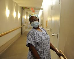 A caregiver poses in the hallway of the residence