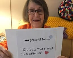 """A Revera resident holds a sign that reads, """"I am grateful for terrific staff that look after us!"""""""