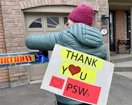 """A woman holds a sign reading """"Thank you PSWs"""""""