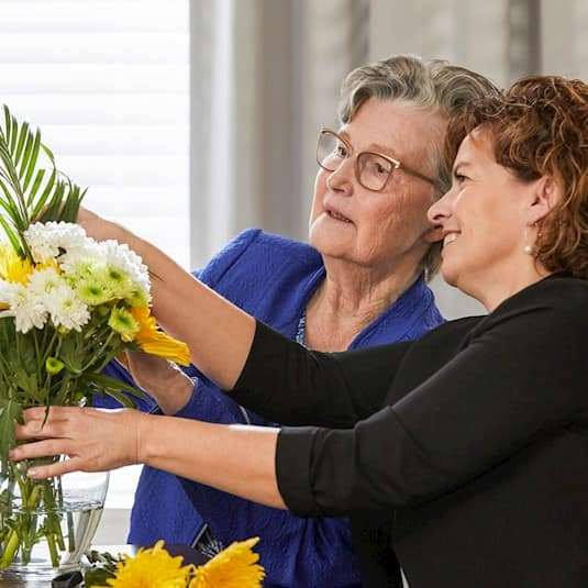 Two ladies arranging flowers
