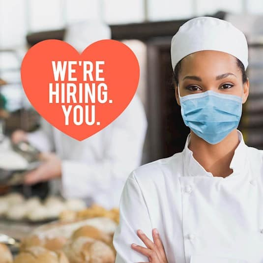"A chef in PPE with a heart showing the words ""We're hiring. You."""