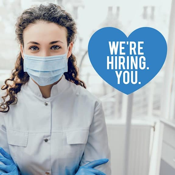 "A nurse wearing PPE with a heart that reads ""We're hiring. You."""