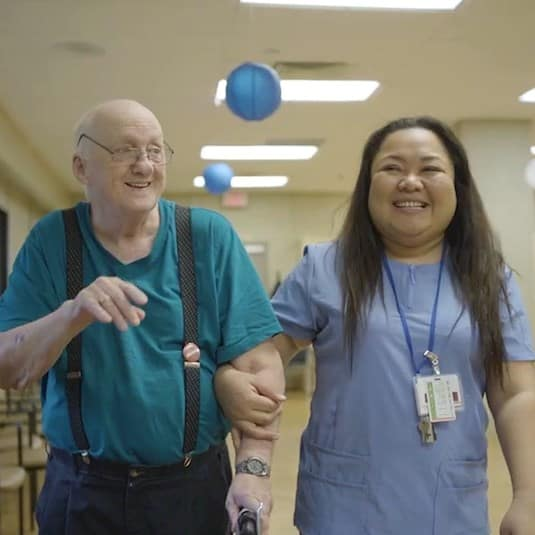 A Registered Practical Nurse walking down the hallway with a resident