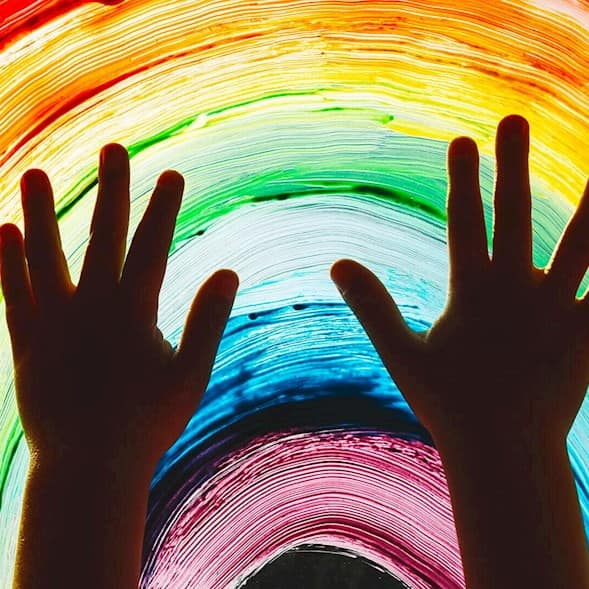 A child's hands in silhouette over a rainbow painted on a window