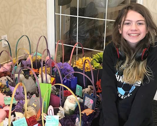 A young girl poses beside gift baskets for Revera residents for Mother's Day