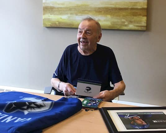 A Revera resident opens a package sent by the Vancouver Canucks