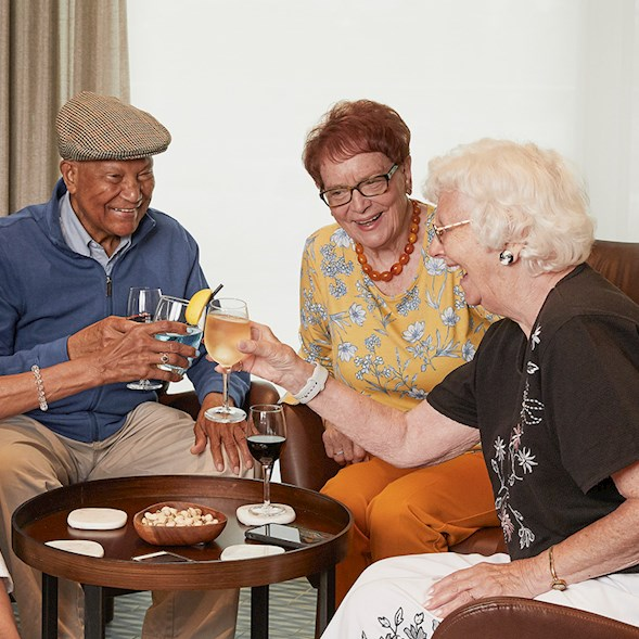 4 older adults sharing a glass of wine and laughing