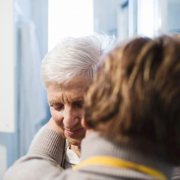 A caregiver assisting an older woman in the activities of daily living