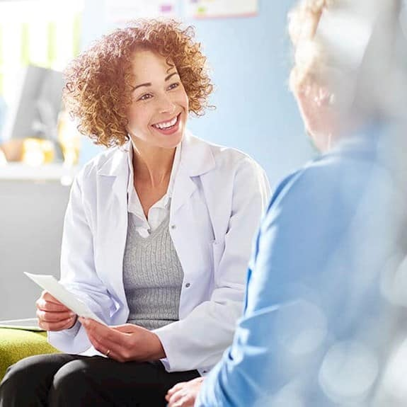 A pharmacist discusses medications with an older woman