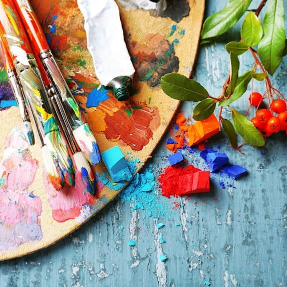 An artist's palette with oil paints, brushes, and pastels