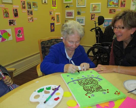 A resident of Royal City Manor adds the finishing touches to her artwork
