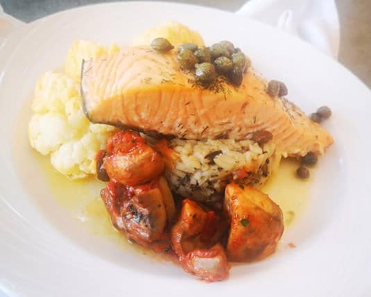 Hand-cut salmon with garlic caper butter on wild rice with cauliflower and roasted peppers