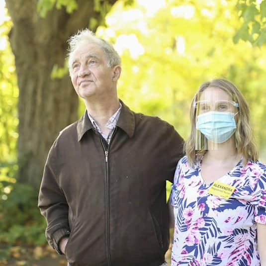 A senior and a care worker, both wearing PPE, standing together