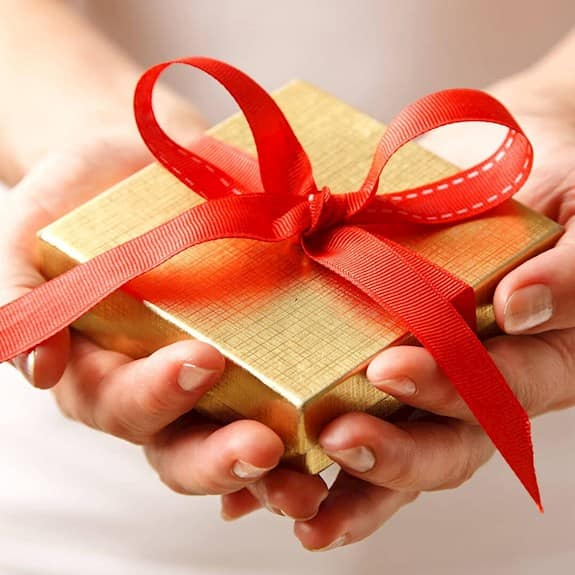 A gold gift box with a red ribbon being held in a person's hands