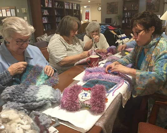 A group of Revera's Knotty Knitters sit around a table working on more twiddlemuffs