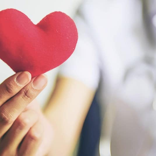 A close-up image of a hand holding a sewn fabric heart