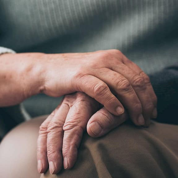 An older man has his hand on his knee, and an older woman's hand is covering his