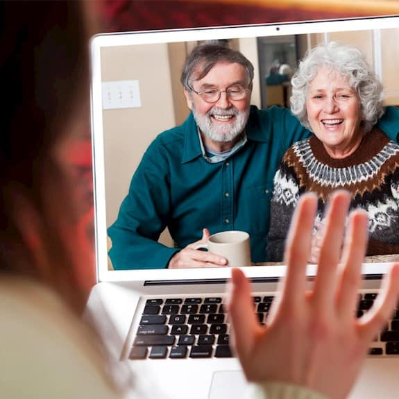 A woman is seen video chatting with a senior couple