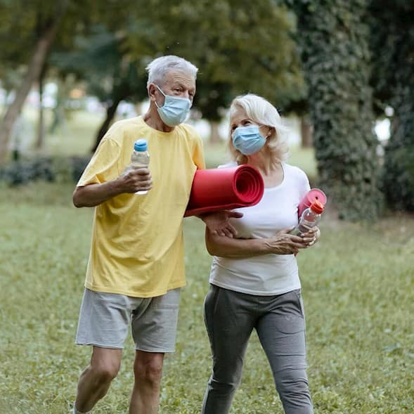 A man and a woman wearing personal protective masks walking side by side carrying yoga mats and bottles of water