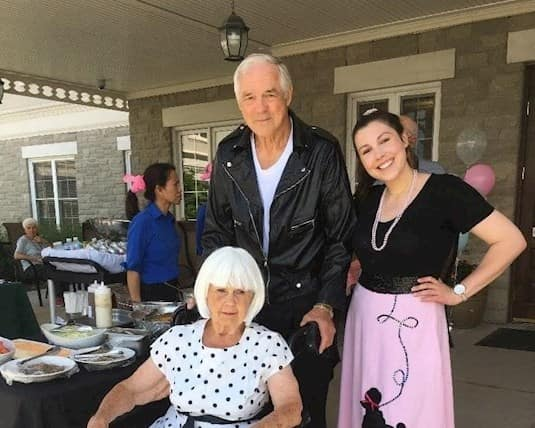 Alyssa poses with two residents for their 1950s themed BBQ