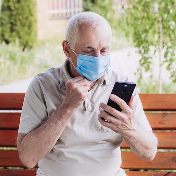 An man, wearing a mask, sits on a bench looking at his phone