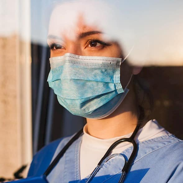 A caregiver dressed in personal protective equipment looks out the window towards the setting sun