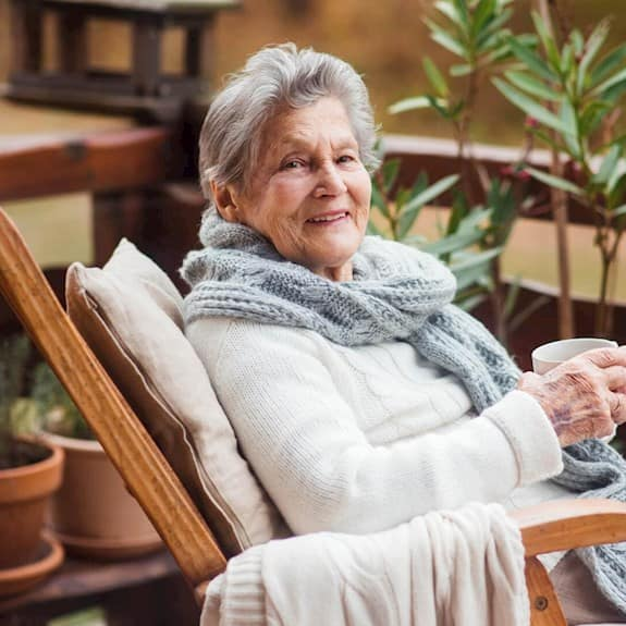 A woman sitting outside with a cup of coffee