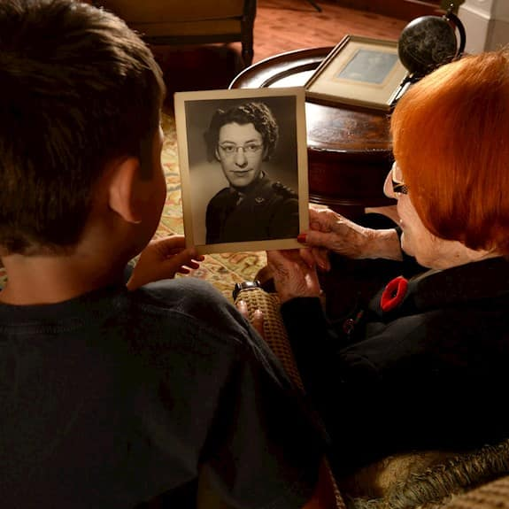 Looking over the shoulder of an older woman and a youth, while they study a photo of the older woman in her youth