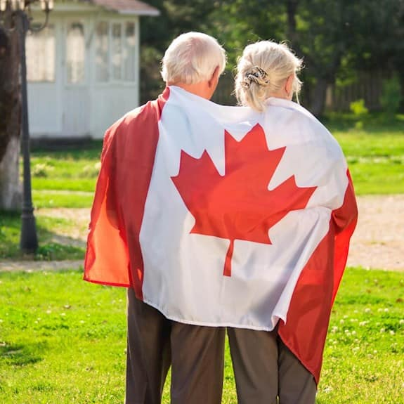 An older couple faces away from the camera, while wearing a Canada flag wrapped around them