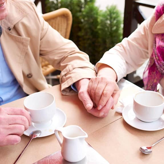 Older couple drinking tea and holding hands