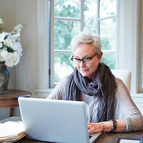 A stylish older woman sitting at her laptop at home