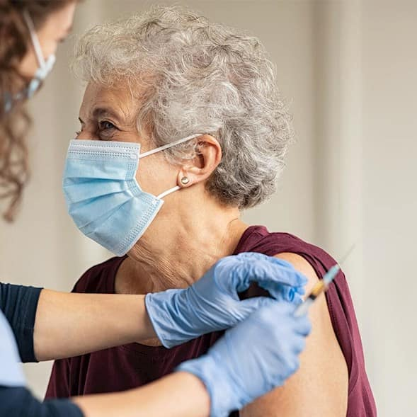 A caregiver prepares to give an older woman a vaccine