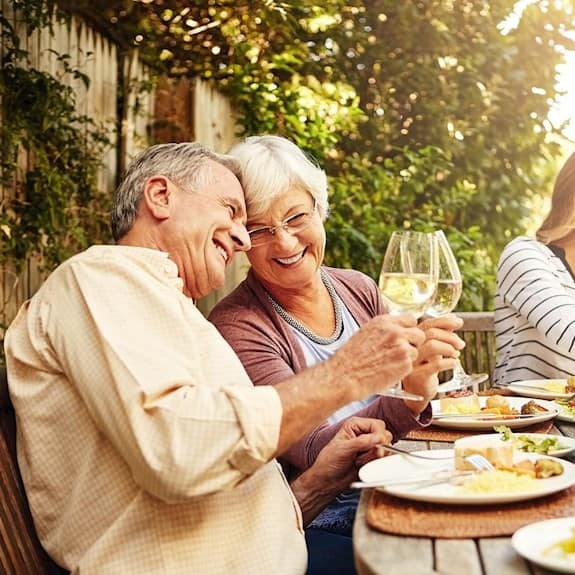 An older couple share a glass of wine at a family party