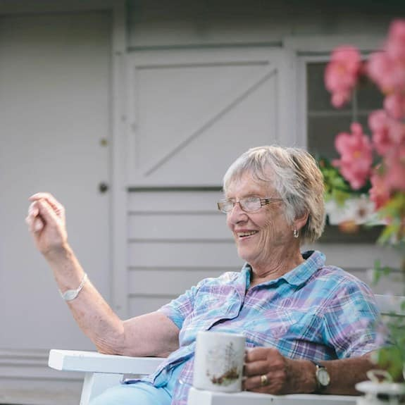 Older woman excitedly chatting while having tea