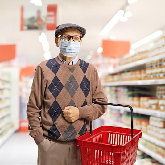 A senior man stands in the centre of a grocery aisle, wearing a PPE mask and holding a shopping basket