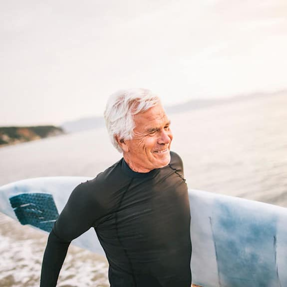 An older man carries a surfboard and smiling